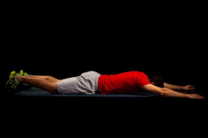 20 Sekunden Superman. Sprunggelenke gestreckt, Arme seitlich vor dem Körper, die Schulterblätter fest nach hinten unten ziehen. Gesäß, unteren und oberen Rücken anspannen, sodass sich Beine und Oberkörper vom Boden lösen – langsam absenken und wiederholen.