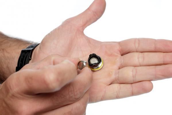 Wir legen neue Batterien in die Abdeckungen ein und achten dabei auf die korrekte Ausrichtung der Pole.