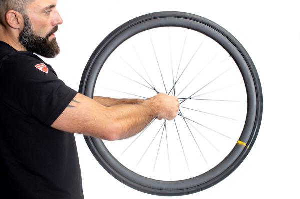 Das Laufrad drehen und etwaig austretende Milch an den Reifenflanken wegwischen.