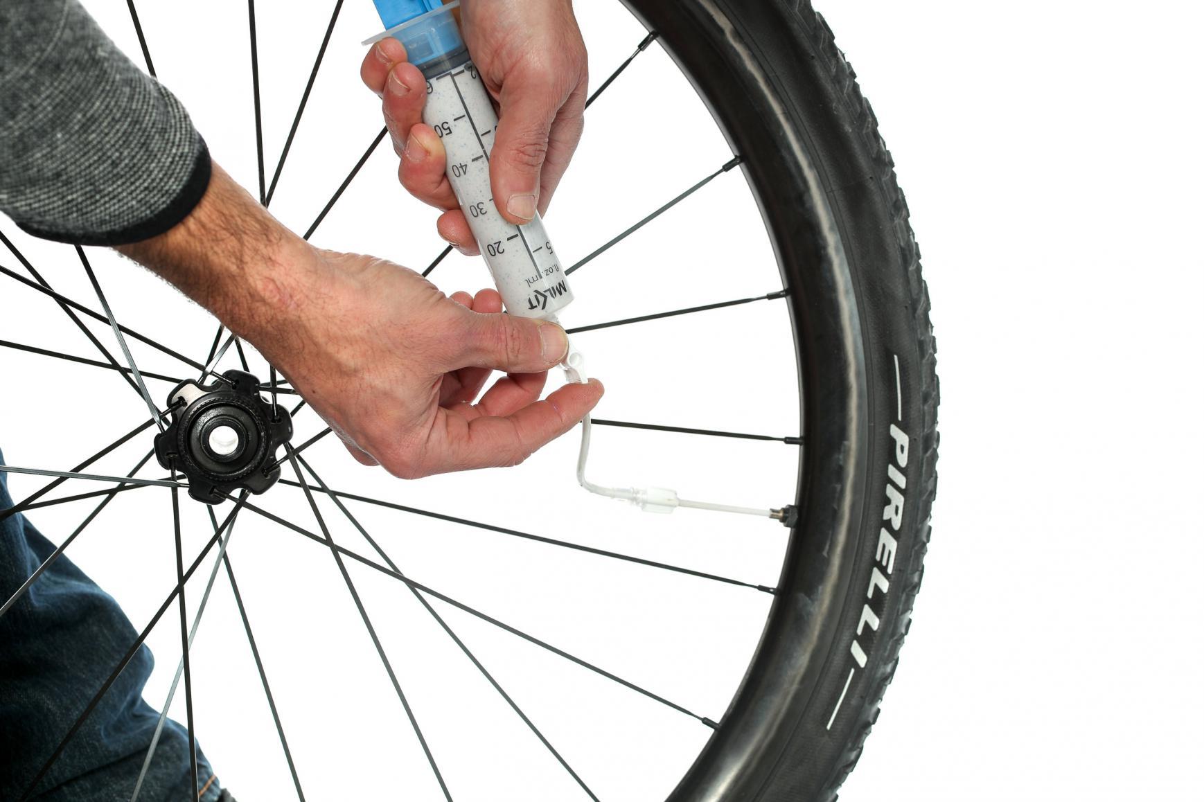 Das Tubeless-Sealant ins Laufrad-Reifen-System einfüllen.