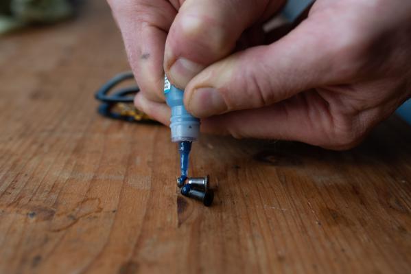 Die beiden Schrauben zur Seite legen und gleich die Schraubensicherung dazu legen.