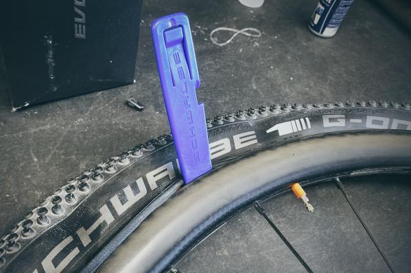 Wir beginnen mit dem Rüberwutzeln des Reifens GEGENÜBER DES VENTILS (!) und hebeln das Ende vom Reifenwulst vorsichtig mit dem Reifenheber über die Felgenflanke.
