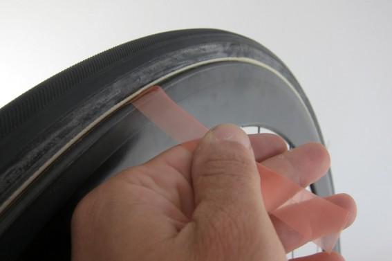 Nun ziehen wir vorsichtig die Schutzfolie zwischen dem Klebeband und dem Reifen heraus und achten darauf, dass es nicht einreißt.