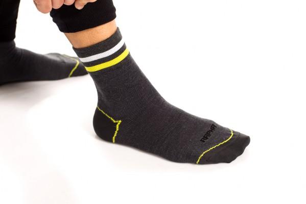 Die Merino Socken mit längerem, dicken Schaft tragen einen weißen Streifen und einen in Signalfarbe.